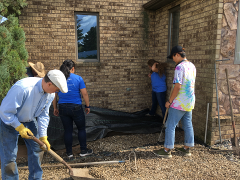 Faculty and students working on repairing gravel outside a building
