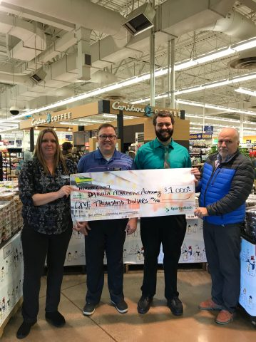 Dakota Adventist Academy receiving a check from Dan's Supermarket for $1,000.